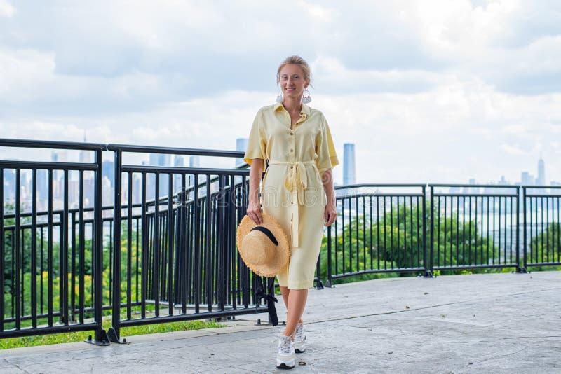 Attraktive junge Frau, die zur Kamera schaut und auf New- York Cityhintergrund lächelt stockbilder