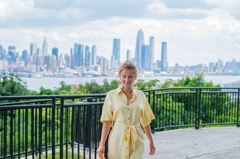 Attraktive junge Frau, die zur Kamera schaut und auf New- York Cityhintergrund lächelt lizenzfreies stockfoto