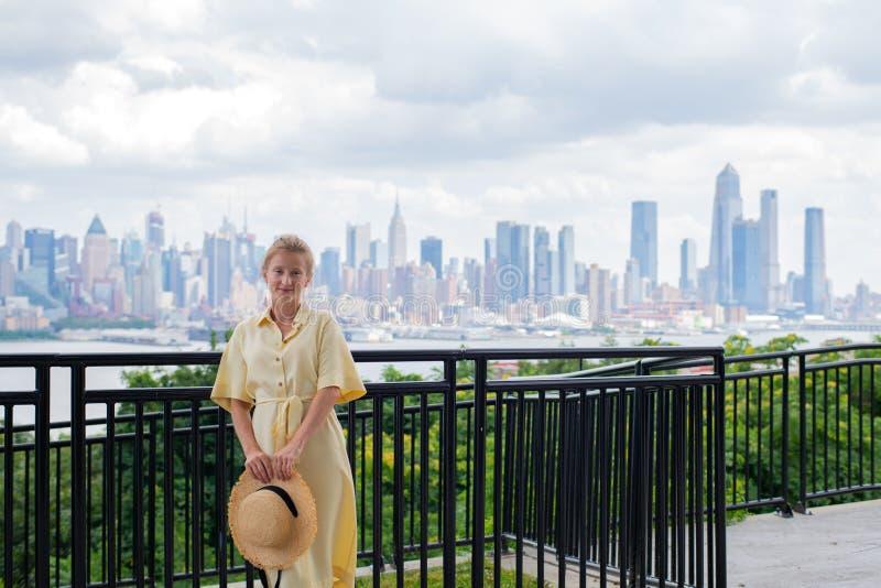 Attraktive junge Frau, die zur Kamera schaut und auf New- York Cityhintergrund lächelt lizenzfreie stockfotos