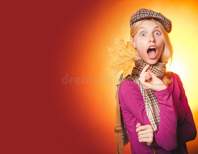 Attraktive junge Frau in einem Saisonkleidung whith goldenen Blatt Tragender Pullover der sinnlichen Frau und Betrachten der Kame lizenzfreies stockfoto