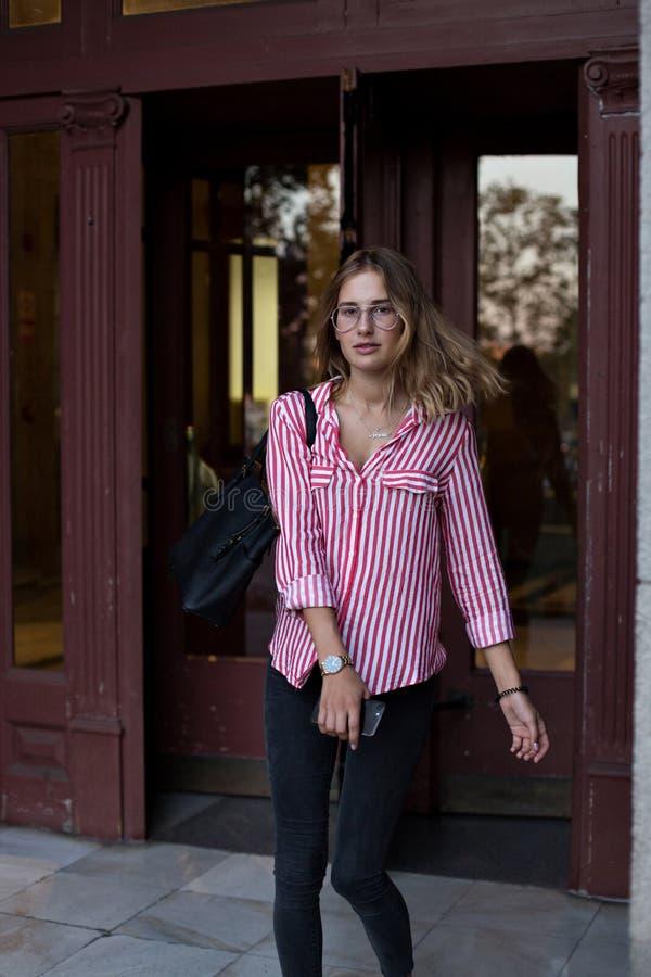Attraktive junge Frau geht durch Drehtüren lizenzfreie stockfotos