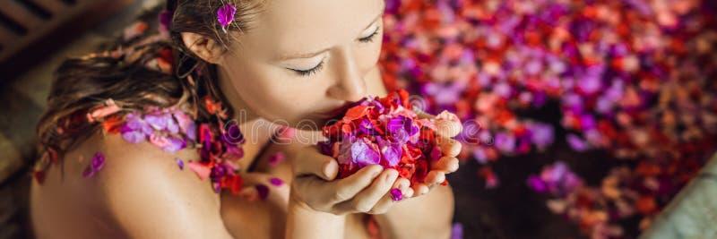 Attraktive junge Frau im Bad mit den Blumenblättern von tropischen Blumen und von Aromaölen Badekuren für Hautverjüngung lizenzfreies stockbild