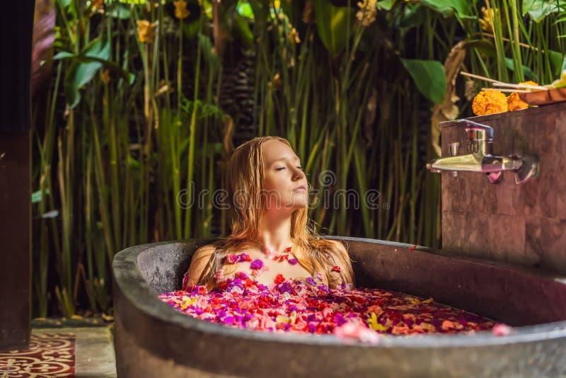 Attraktive junge Frau im Bad mit den Blumenbl?ttern von tropischen Blumen und von Aroma?len Badekuren f?r Hautverj?ngung stockbild