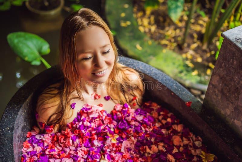 Attraktive junge Frau im Bad mit den Blumenbl?ttern von tropischen Blumen und von Aroma?len Badekuren f?r Hautverj?ngung stockfotos