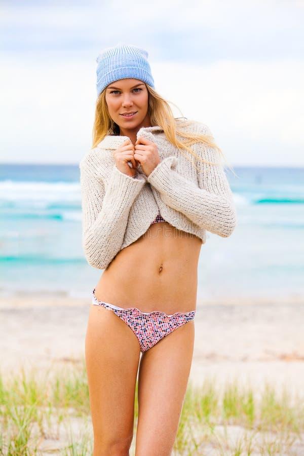 Attraktive junge Frau im Bikini, in der Knit-Schutzkappe und in Schalter stockbild