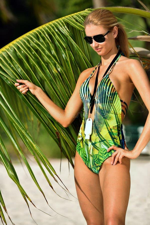 Attraktive junge Frau im Designbadeanzug, der auf dem Strand mit Palme aufwirft stockfoto