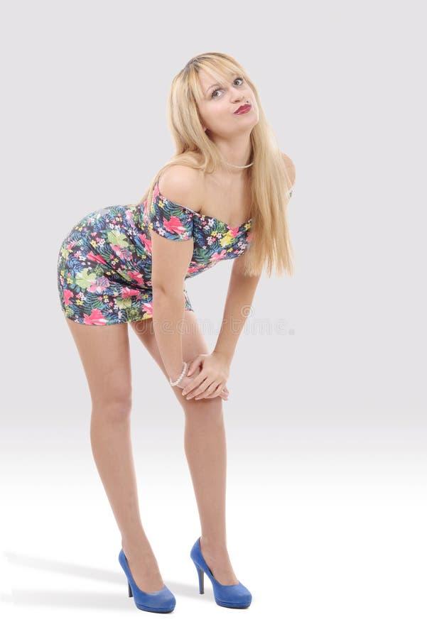 Attraktive junge Frau im kurzen bunten Kleid lizenzfreies stockbild