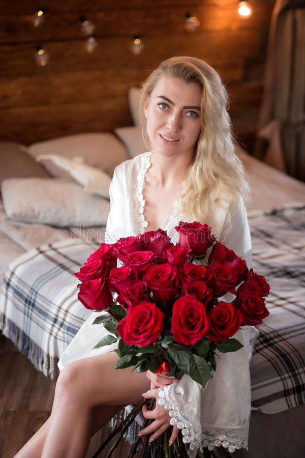 Attraktive junge Frau mit Blumenstrauß von roten Rosen morgens stockbilder