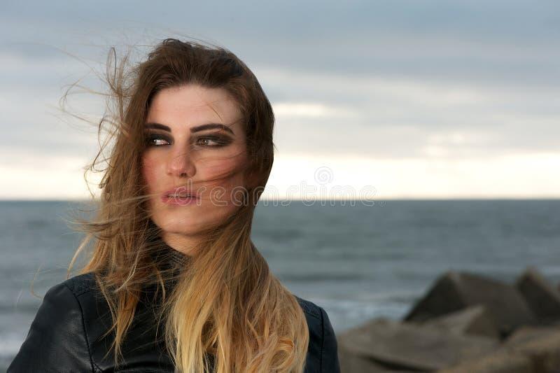 Attraktive junge Frau mit dem Schlaghaar des Winds draußen stockbilder