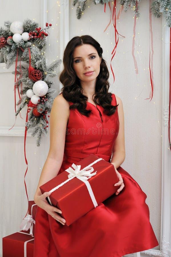 Attraktive junge Frau mit einem Weihnachtsgeschenk stockfotografie