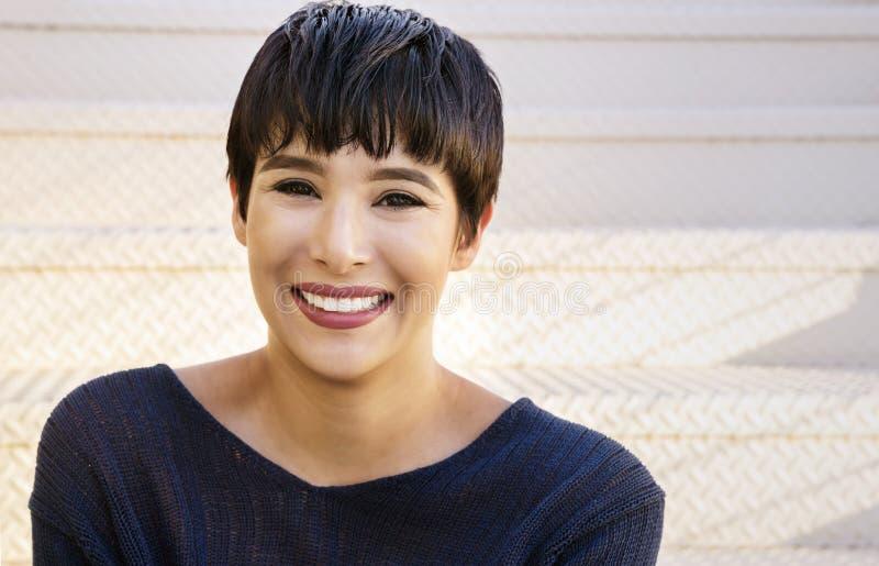 Attraktive junge Frau mit freundlichem Lächeln des kurzen stilvollen Haares stockbilder