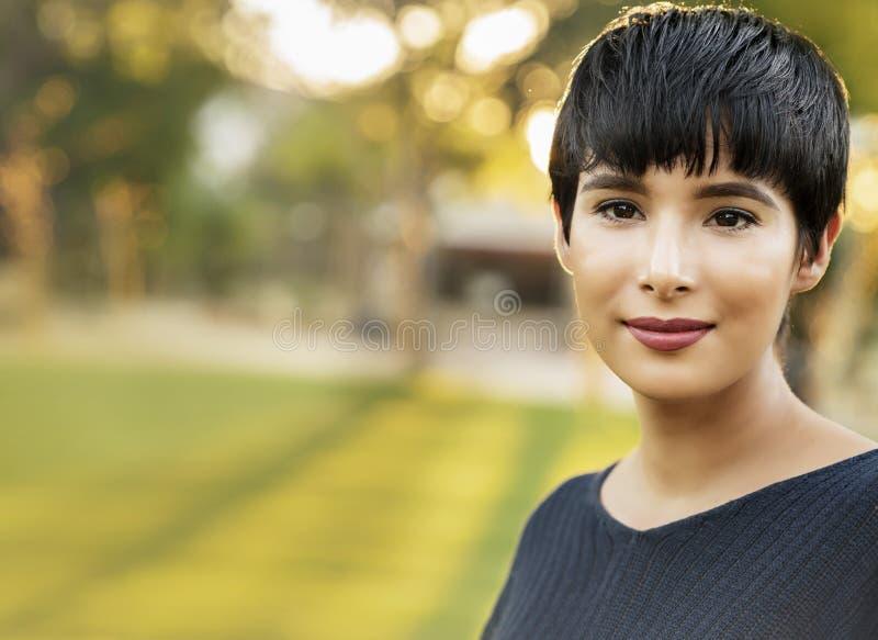 Attraktive junge Frau mit freundlichem Lächeln des kurzen stilvollen Haares lizenzfreies stockbild