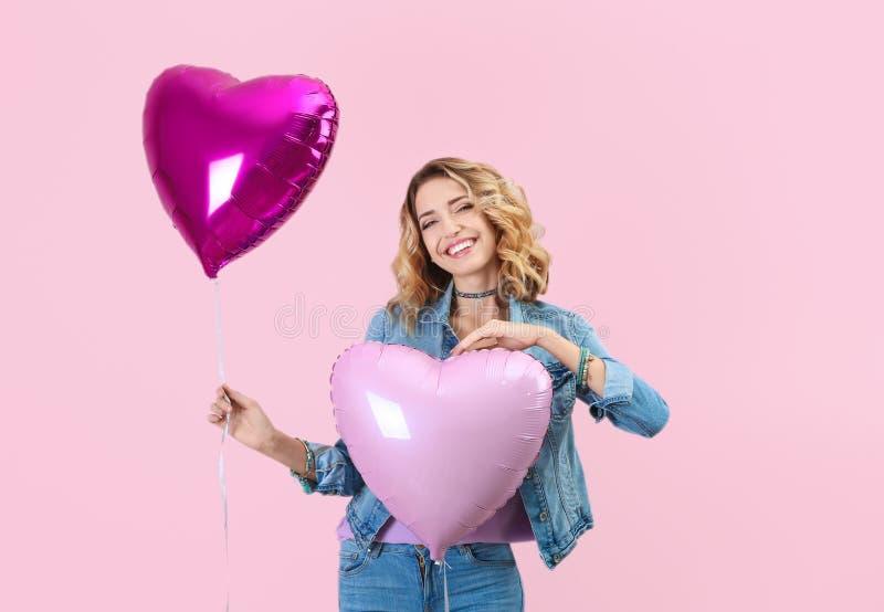 Attraktive junge Frau mit Herzen formte Luftballone stockfotos