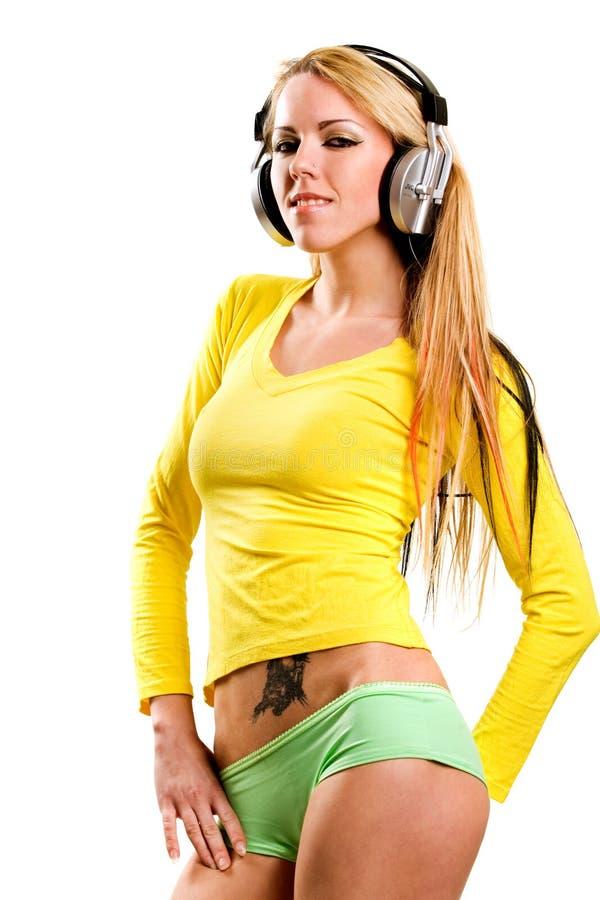 Attraktive junge Frau mit Kopfhörern über Weiß stockfotos