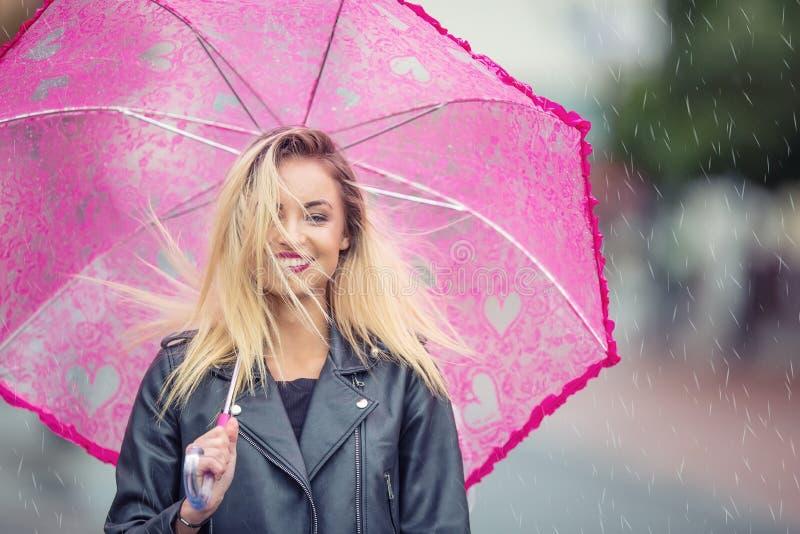 Attraktive junge Frau mit rosa Regenschirm im Regen und im starken Wind Mädchen mit Regenschirm im Herbstwetter lizenzfreie stockfotografie