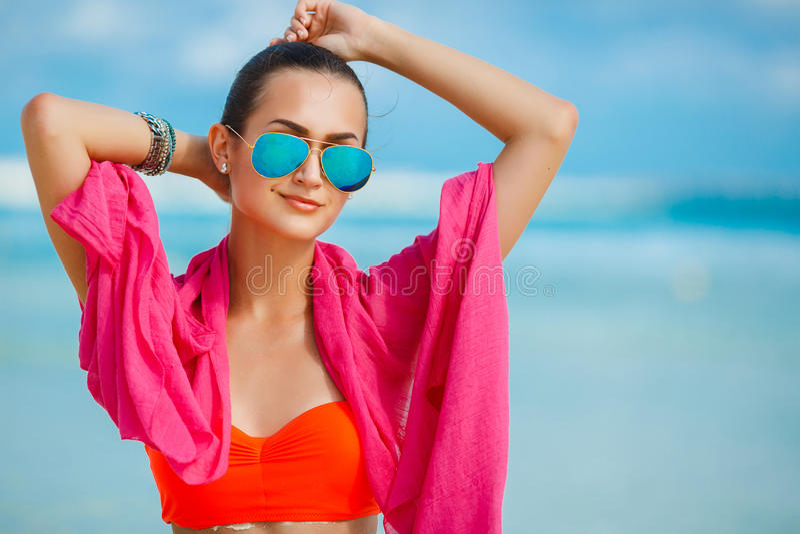 Attraktive junge Frau mit rotem pareo auf dem Strand lizenzfreie stockfotos