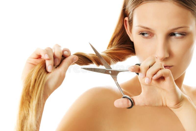 Attraktive junge Frau schneidet ihr langes natürliches Haar stockfoto