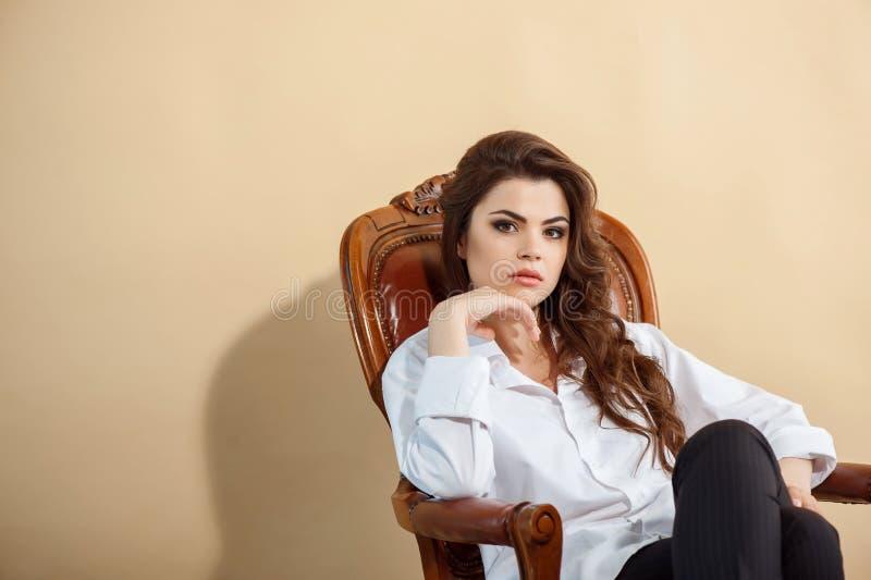 Attraktive junge Frau sitzt im Stuhl lizenzfreie stockfotos