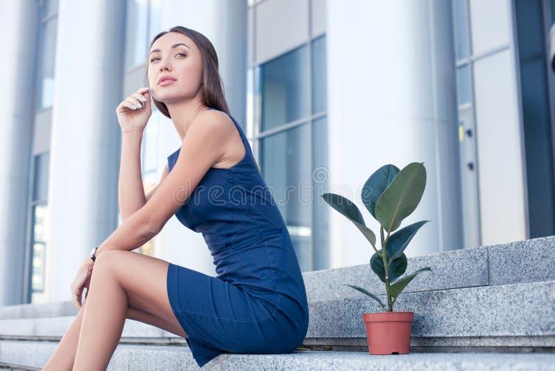 Attraktive junge Frau steht nahe ihrem Büro still lizenzfreie stockfotos