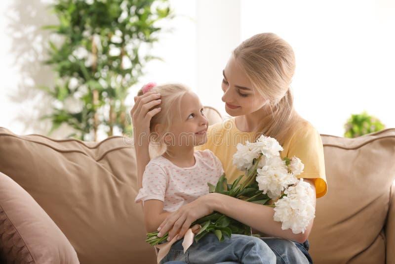 Attraktive junge Frau und nettes kleines Mädchen mit den schönen Blumen, die zu Hause auf Sofa sitzen lizenzfreie stockfotos