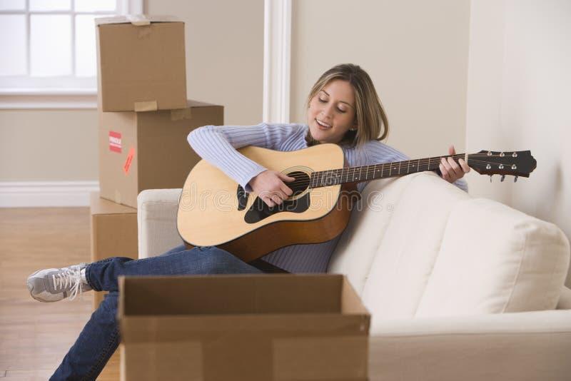 Attraktive junge Frau, welche die Gitarre spielt stockfotos