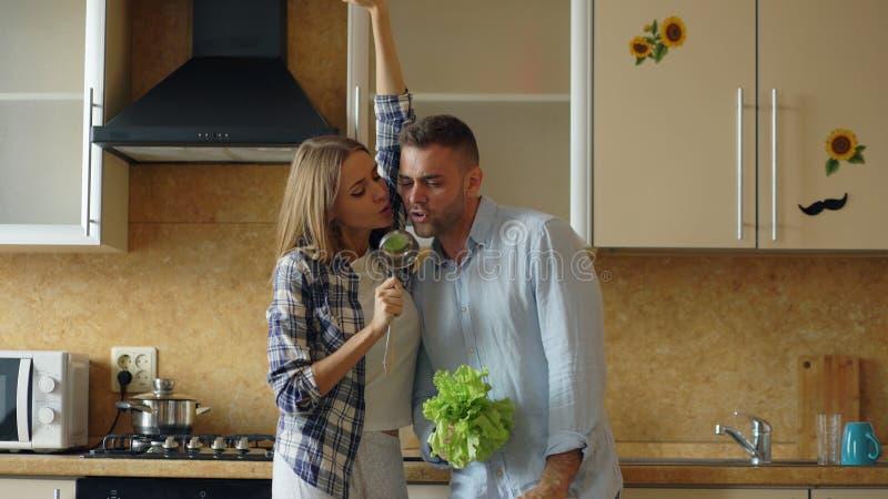 Attraktive junge frohe Paare haben Spaßtanzen und den Gesang beim zu Hause kochen in der Küche stockbilder