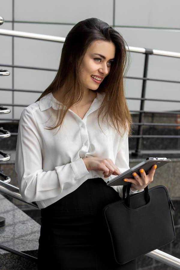 Attraktive junge Geschäft Dame im weißen Hemd, das ein Tablet hält stockfoto
