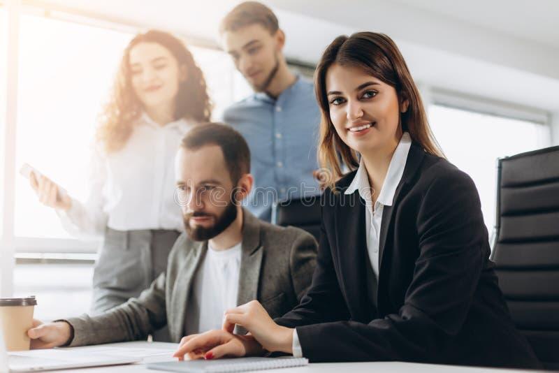 Attraktive junge Geschäftsdame betrachtet Kamera und lächelt, während ihre Kollegen im Hintergrund arbeiten stockfotos