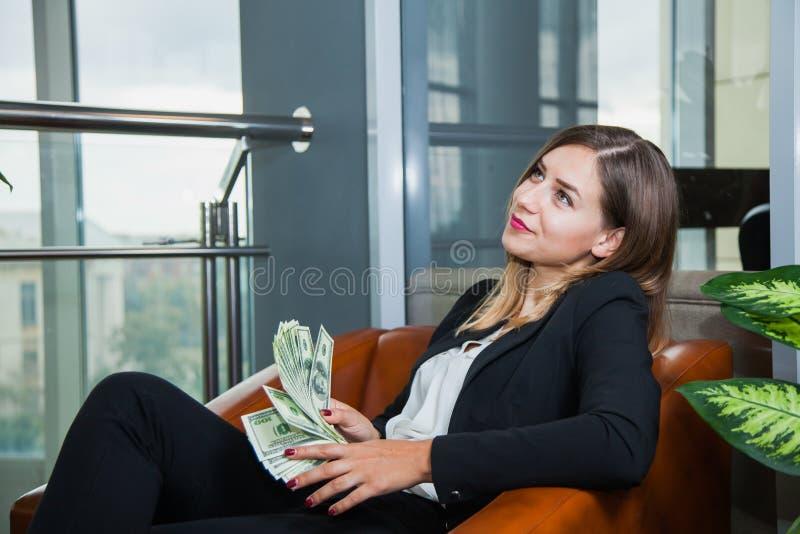 Attraktive junge Geschäftsfrau, die Gelddollar und -lächeln zählt stockfotografie