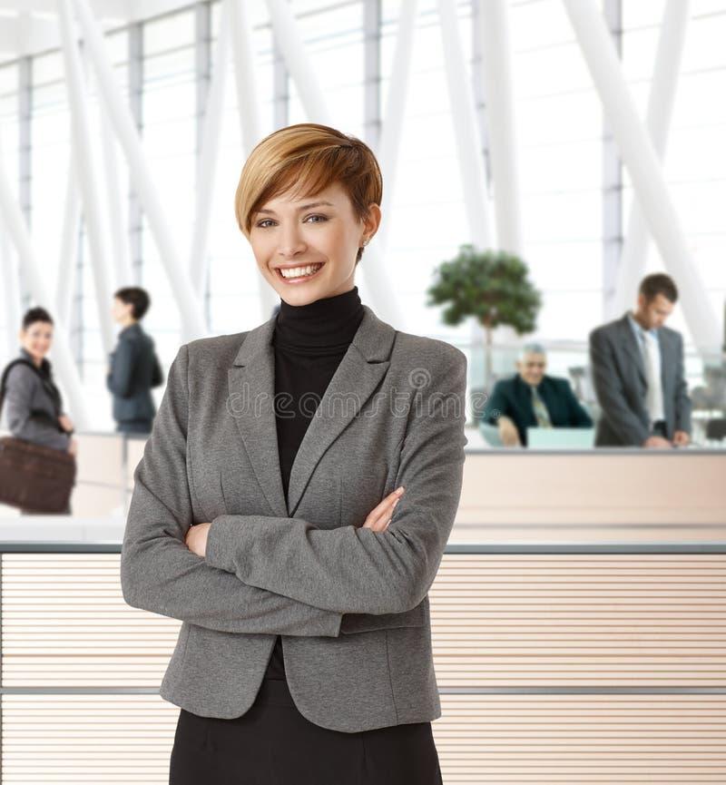 Attraktive junge Geschäftsfrau im Büroflur stockfotografie