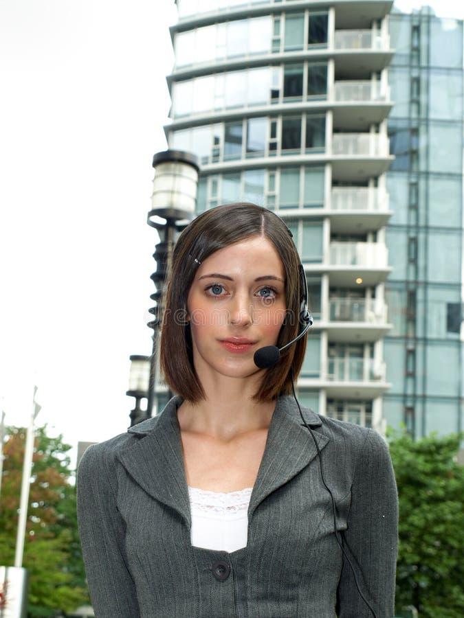 Attraktive junge Geschäftsfrau mit Kopfhörer lizenzfreie stockfotografie