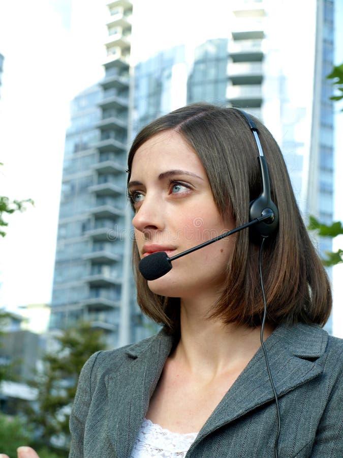 Attraktive junge Geschäftsfrau mit Kopfhörer stockbild