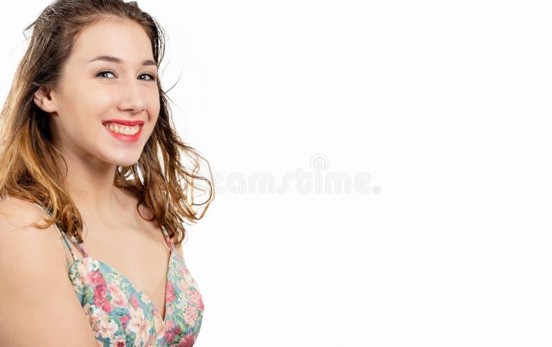 Attraktive junge lächelnde Frau auf einem weißen Hintergrund lizenzfreie stockfotos