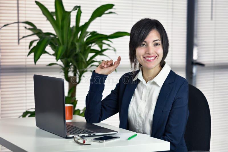 Attraktive junge lächelnde Frau des Geschäfts beim Sitzen an ihrem wor lizenzfreies stockbild