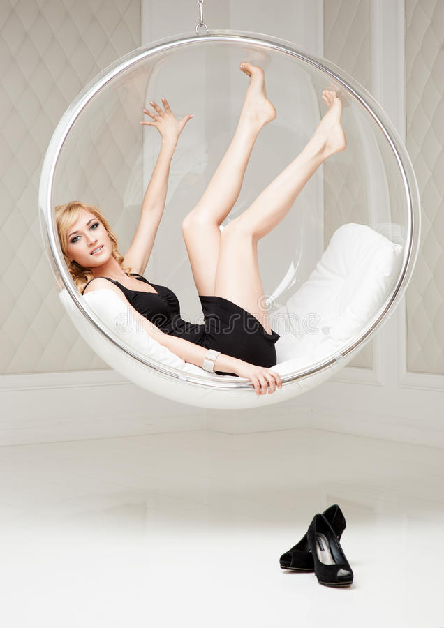 Attraktive junge lächelnde Frau, die im runden Stuhl liegt stockbild