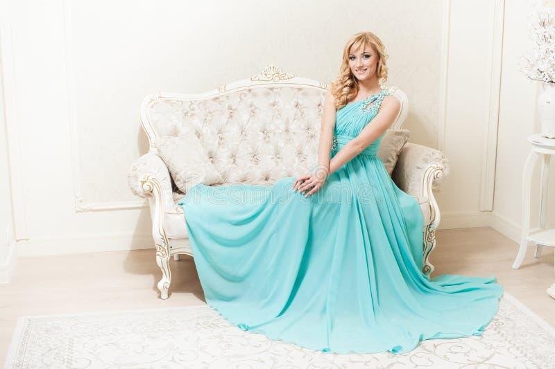 Attraktive junge lächelnde Frau, die am Sofa sitzt lizenzfreie stockfotos