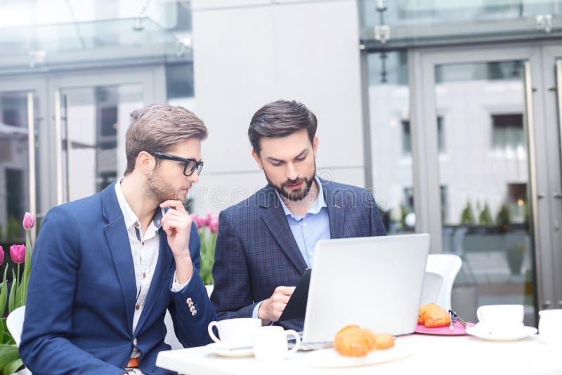 Attraktive junge Männer essen einen Business-Lunch zu Mittag stockbilder
