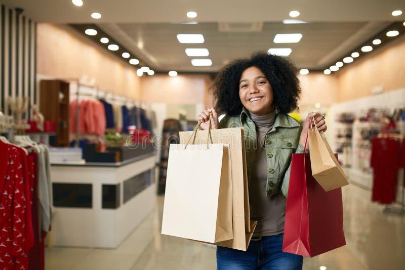 Attraktive junge nette Afroamerikanerfrau, die mit Einkaufstaschen mit Bekleidungsgeschäft auf backgroud aufwirft Recht Schwarzes stockfotos