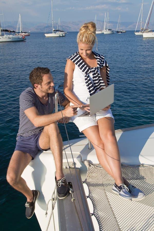 Attraktive junge Paare auf dem Segelboot, das Laptop betrachtet. lizenzfreie stockfotos