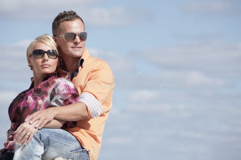 Attraktive junge Paare auf einem Hintergrund des bewölkten Himmels stockfotos