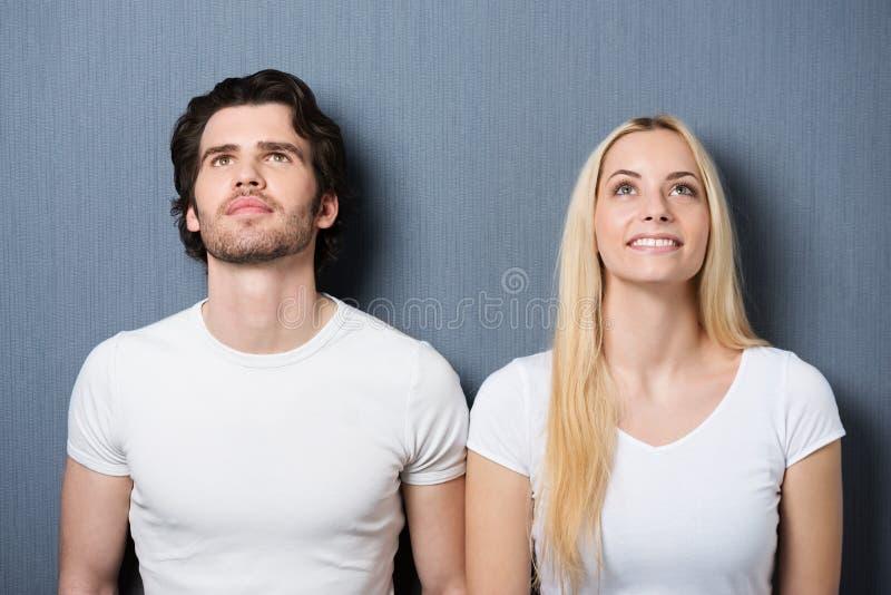 Attraktive junge Paare, die denkend stehen stockfotos