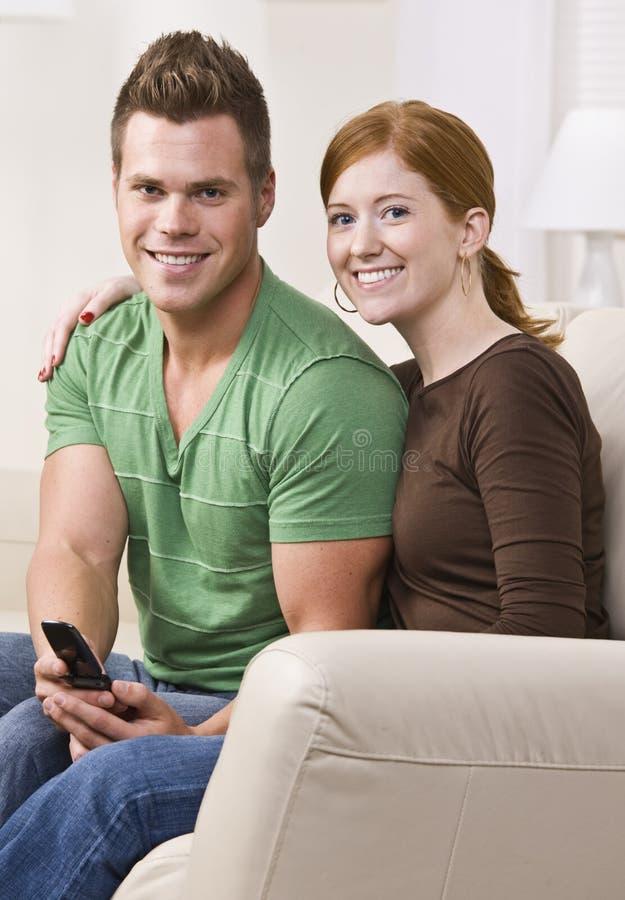 Attraktive junge Paare, die zusammen auf Couch sitzen stockbild