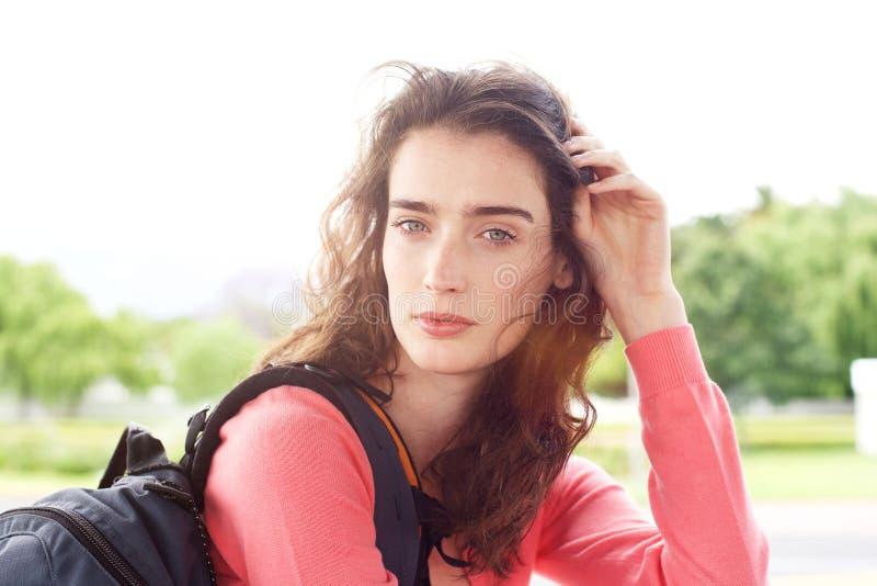 Attraktive junge Reisendfrau mit der Hand im Haar und im Rucksack lizenzfreie stockbilder