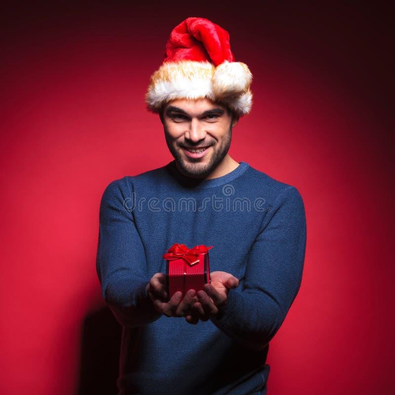 Attraktive junge Sankt, die Ihnen ein kleines rotes Geschenk gibt lizenzfreie stockfotografie