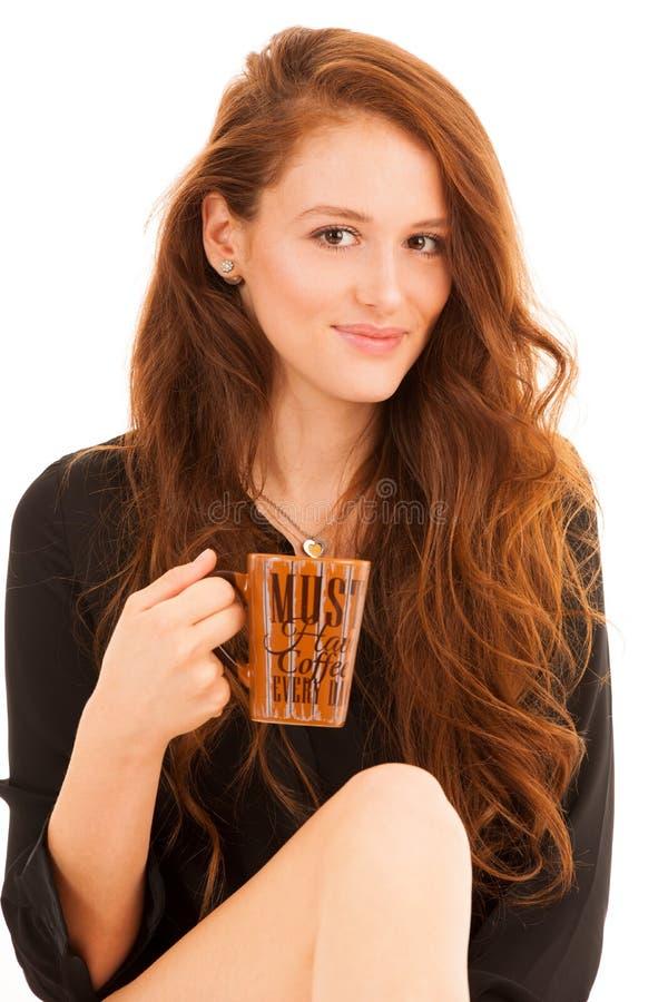 Attraktive junge schöne Brunettefrau, die auf ihrem Bett sitzt und stockbilder