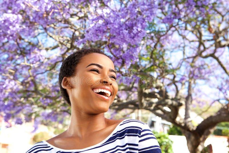 Attraktive junge schwarze Frau, die draußen durch Blumenbaum lacht stockfotos