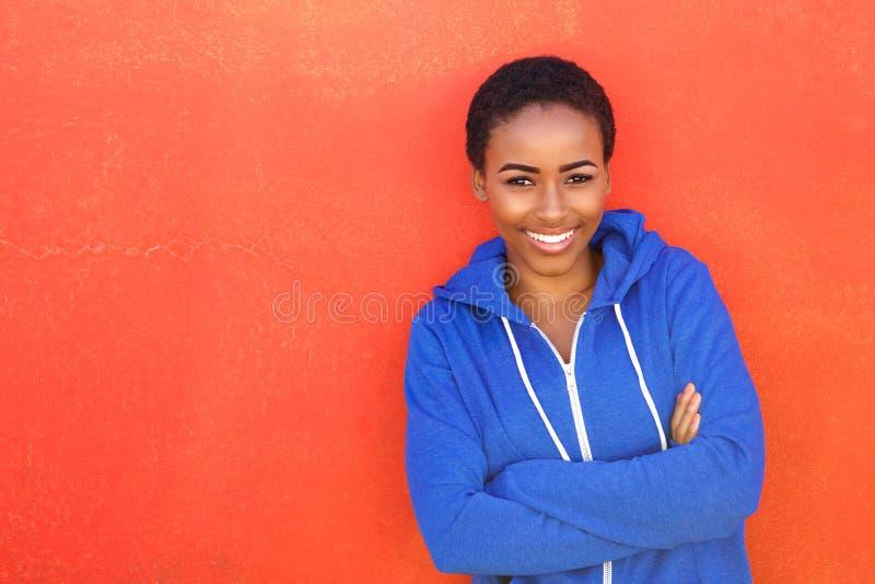 Attraktive junge schwarze Frau, die gegen roten Hintergrund lächelt lizenzfreie stockbilder