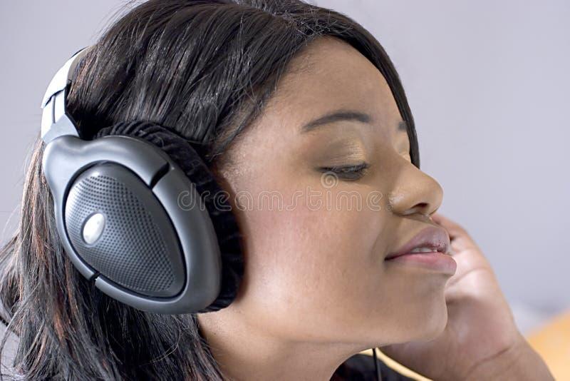 Attraktive junge schwarze Frau, die Musik hört lizenzfreie stockbilder