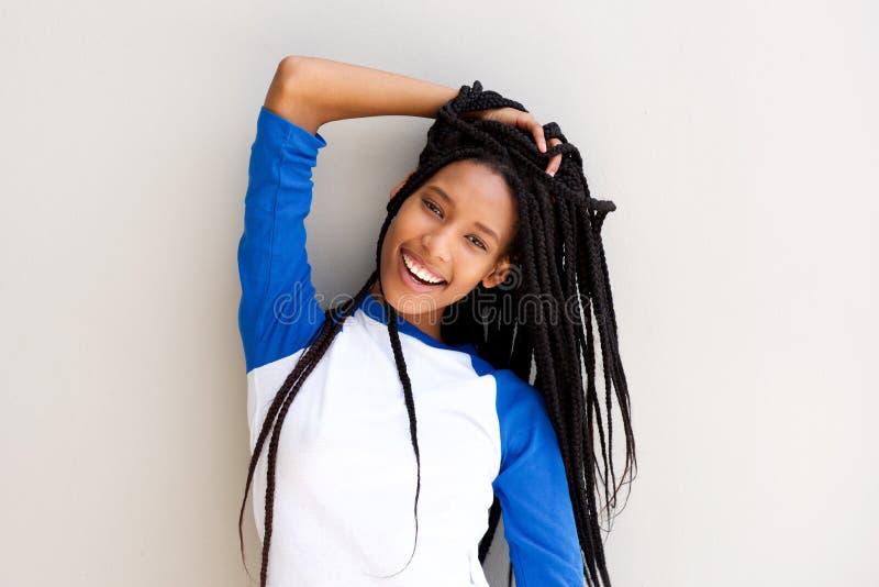 Attraktive junge schwarze Frau mit dem umsponnenen Haar, das gegen eine Wand aufwirft lizenzfreies stockfoto