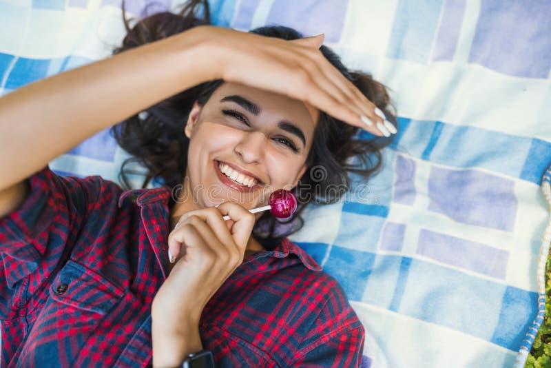 Attraktive junge sexy brunette Frau, in der Hand lächelnd mit Lutscher, kariertes Hemd tragend, liegend auf dem Gras im Parkgenie lizenzfreie stockfotografie